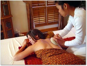 woman getting massage with herbal bag