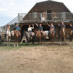 wranglers holding hats up at Big Bar Guest Ranch