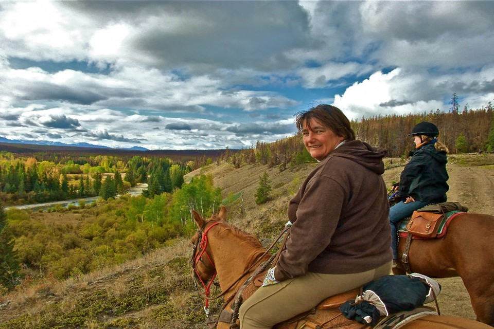woman on horses looking at river at Big Creek