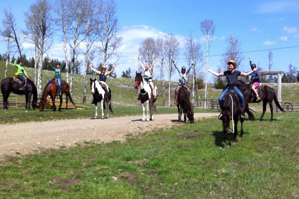 guest ranch guests on horses with arms waving