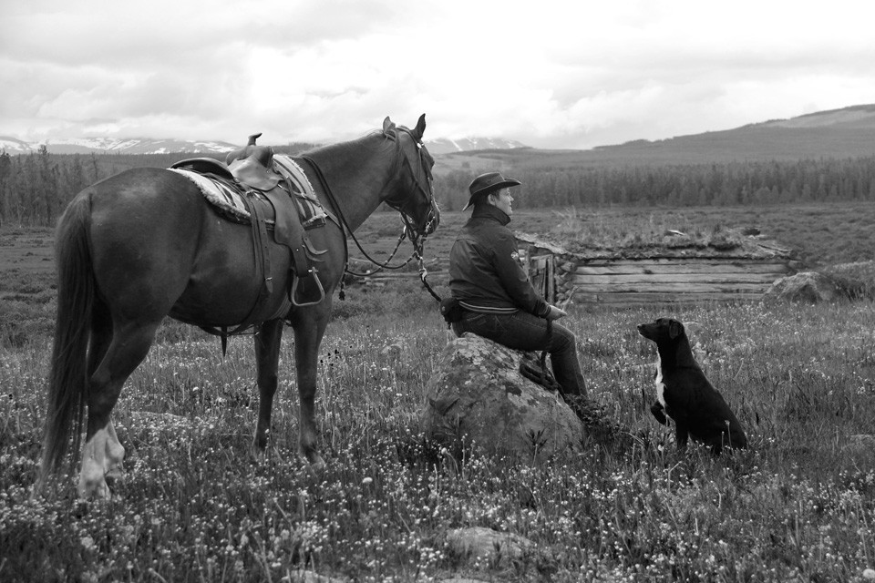black and white photo of rancher with horse and dog