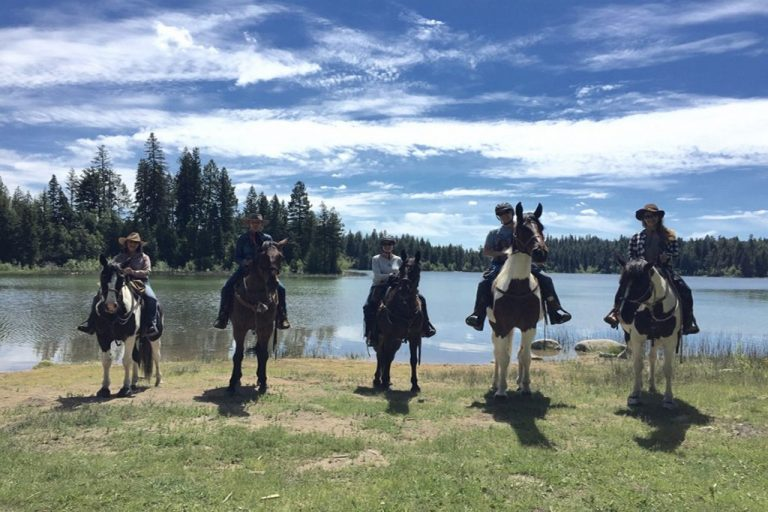 ranchers on horseback in front of lake
