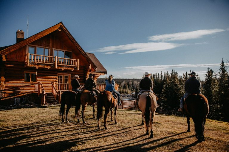 wood lodge with five ranchers and their horses