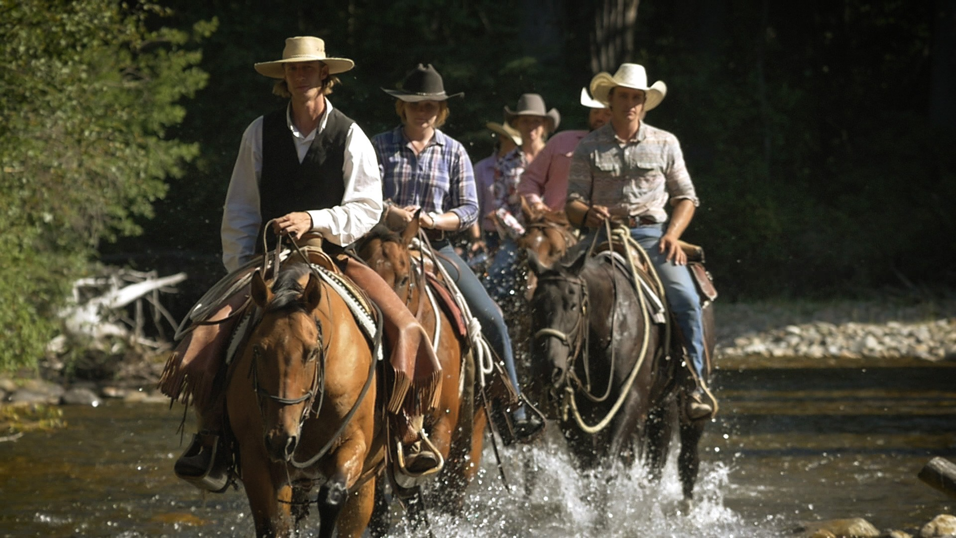 wranglers crossing the river at the ranch